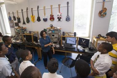 "Intern Shunafrica White, center, tells a group of area middle school students with the M-Cubed program (""Math, Men and Mission"") about her research improving upon a robotic arm."